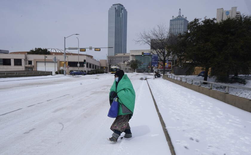 FILE - In this Feb. 16, 2021, file photo, a woman wrapped in a blanket crosses the street near downtown Dallas. As temperatures plunged and snow and ice whipped the state, much of Texas' power grid collapsed, followed by its water systems. Tens of millions huddled in frigid homes that slowly grew colder or fled for safety. (AP Photo/LM Otero, File)