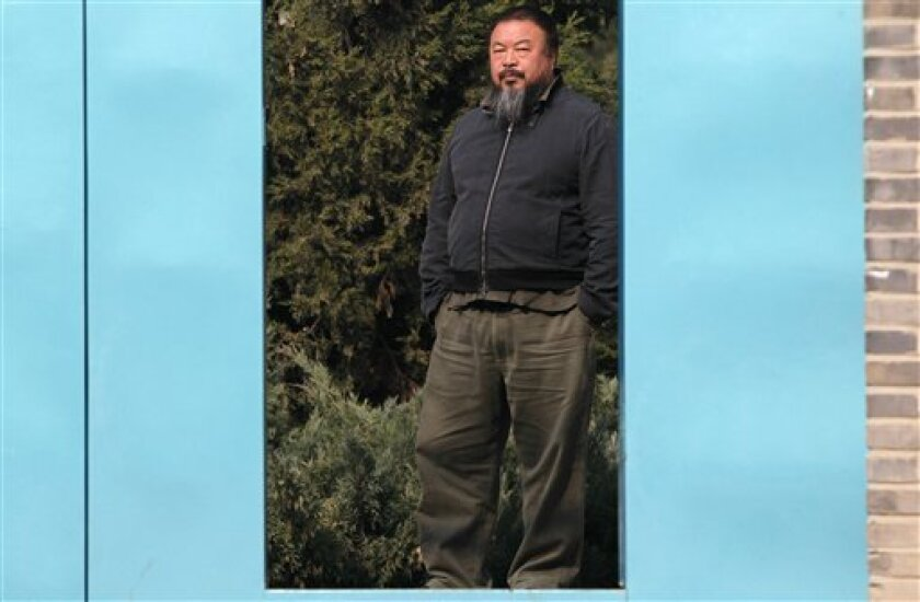 Chinese avant-garde artist Ai Weiwei stands at the doorway to his home where he is under house arrest in Beijing Saturday, Nov. 6, 2010. Ai said Saturday that he has been placed under house arrest to prevent him from attending a party commemorating the forced demolition of his newly built studio in Shanghai. (AP Photo/Ng Han Guan)
