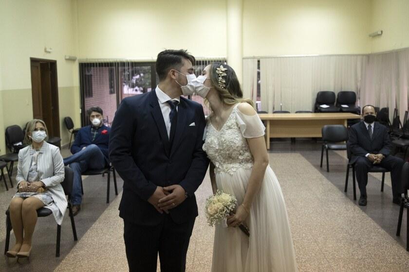 Raúl Benítez y Jenny Bonet se besan luciendo barbijos durante la ceremonia en el registro civil de Asunción