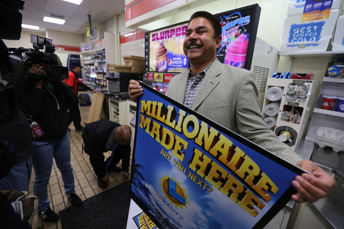 """7-Eleven franchise owner Balbir Atwal holds one of the """"Millionaire Made Here"""" lottery signs in his Chino Hills store, where one of the winning Powerball tickets was sold."""