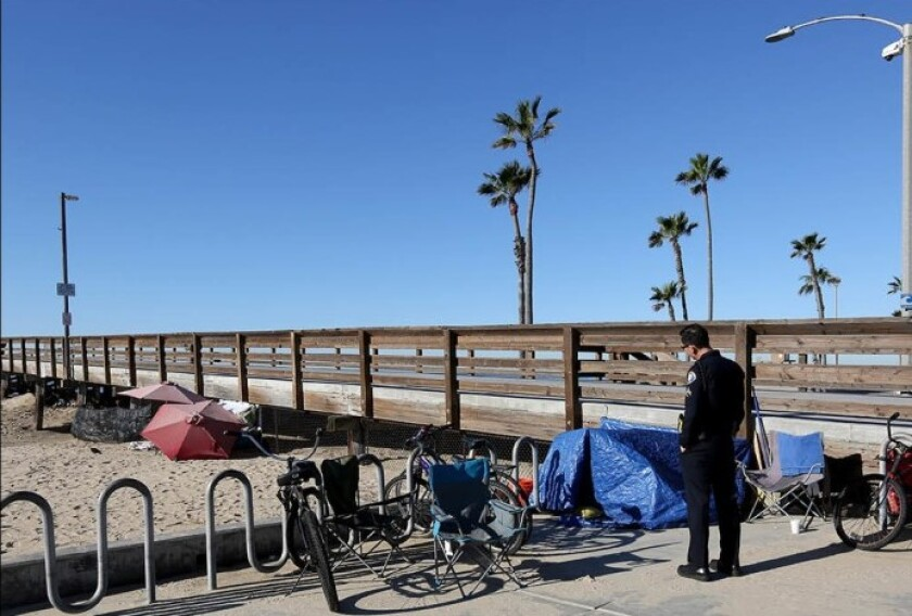 Tony Yim, a homeless liaison officer with the Newport Beach Police Department, speaks with homeless people staying at the Balboa Pier last year. In October, the city posted a request for proposals to run a local homeless shelter. Potential bidders downloaded the documents but did not return any.