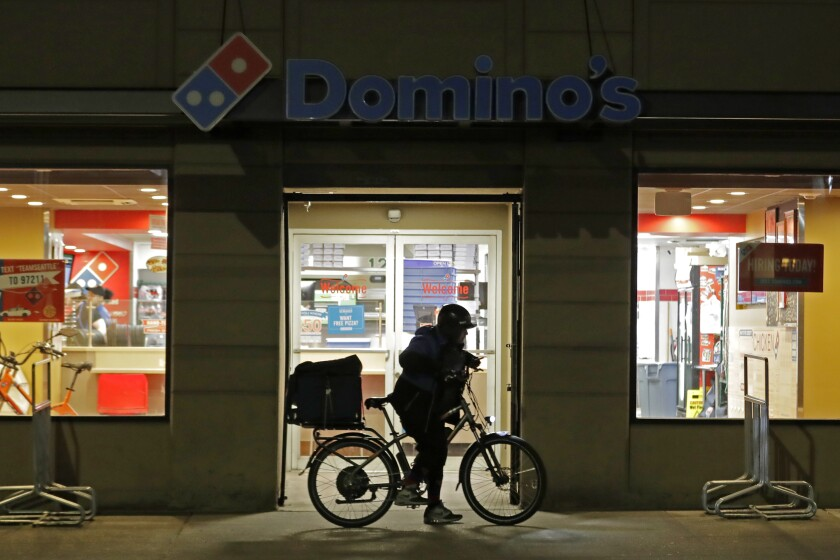 FILE - A delivery worker leaves a Domino's Pizza restaurant in downtown Seattle on a bike, Sunday, March 15, 2020. Domino's Pizza says shortages of cooks, drivers and other staff are pinching sales at its U.S. stores. The world's largest pizza chain said Thursday, Oct. 14, 2021 its same-store sales __ or sales at stores open at least a year __ dropped 1.9% in the July-September period. It was the first time in a decade that the company's U.S. same-store sales have fallen. (AP Photo/Ted S. Warren, file)