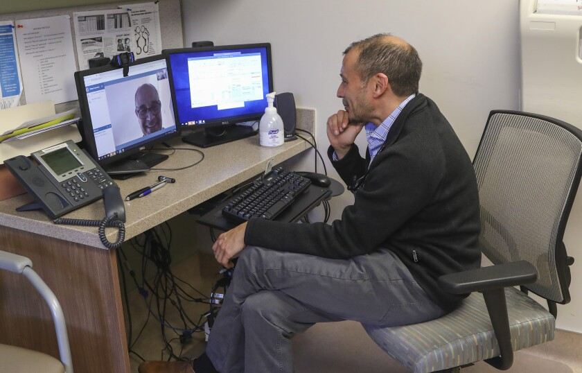 Dr. Nilesh Shah, who is at the VA Sorrento Valley Clinic, works with patient Neil Harrington, who lives in North County. Under certain circumstances, Shah offers patients the ability to have their doctors' visits via a telemedicine system.