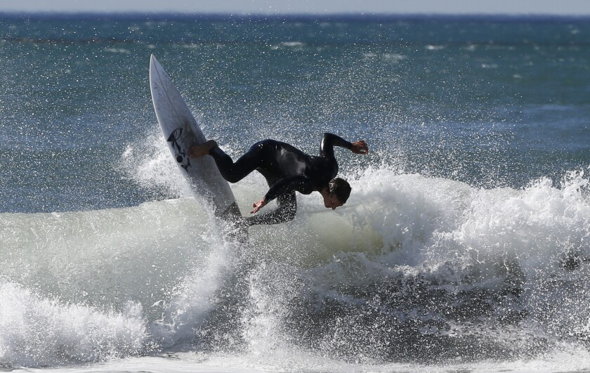 A surfer braves the waves amid strong Santa Ana winds off the Southern California coast, where temperatures topped 80 degrees at the beach Thursday.