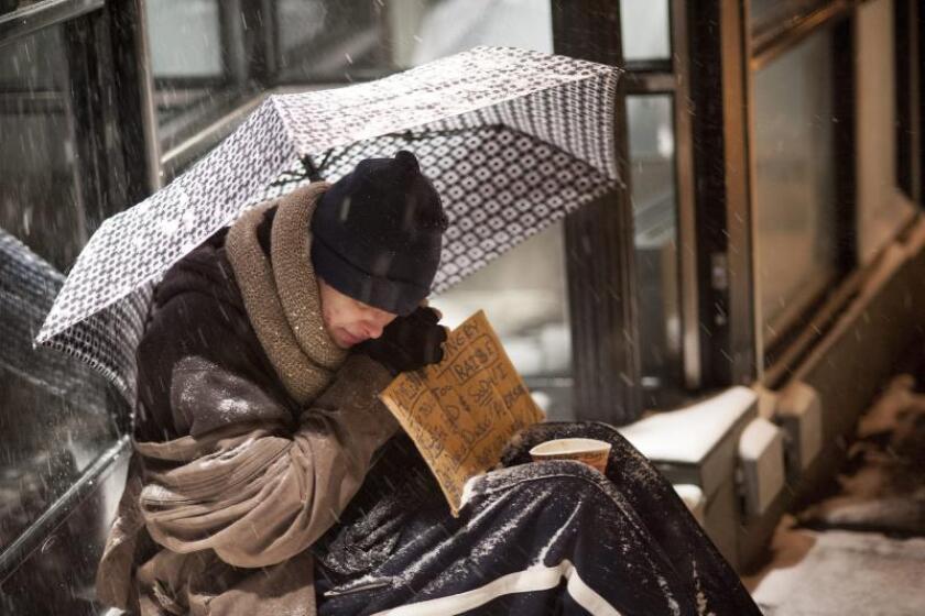 Un sin techo se cubre con un paraguas durante una nevada en Nueva York (Estados Unidos). EFE/Sebastian Gabriel/Archivo