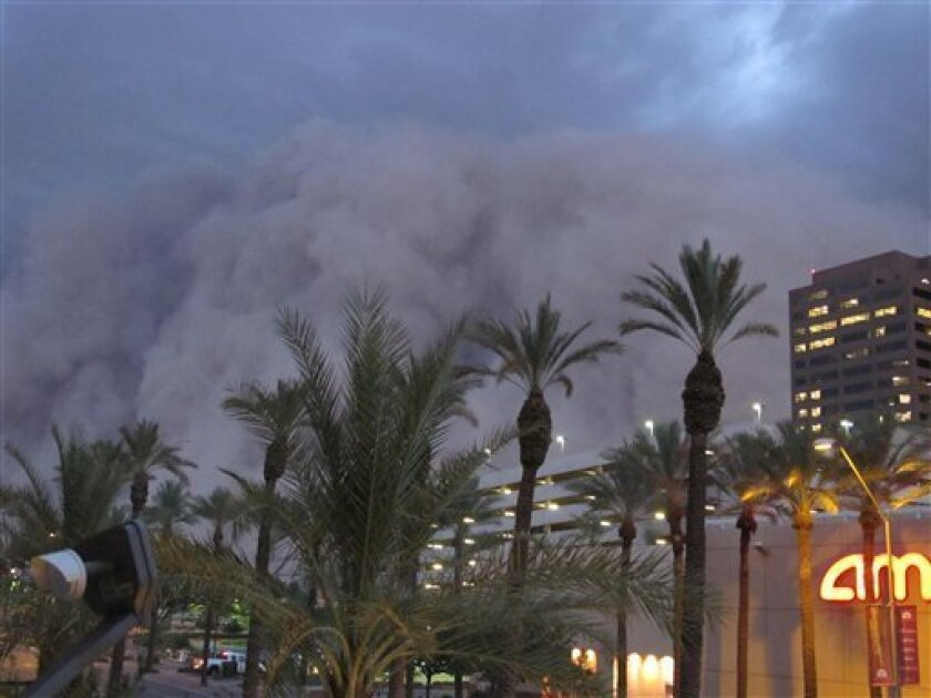 """A dust storm known as a """"habub"""" rolls into downtown Phoenix on Tuesday night, July 5, 2011, bringing strong winds and low visibility. Habubs are part of Arizona's annual monsoon season, which is now in full swing. (AP Photo/Amanda Lee Myers)"""