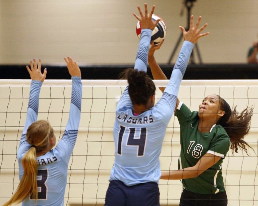 Reagan's Kyla Waiters, right, spikes the ball past Johnson from the Texas District 26-6A high school volleyball match Friday, Sept. 22, 2017. Waiters, who went on to sign a scholarship at Oregon State, was among a half-dozen players who reached out to The Associated Press after a July 2020 story in which players, parents and people familiar with the program said Oregon State coaches physically and emotionally abused some players while the administration took no outward steps to address complaints. (Ron Cortes/The San Antonio Express-News via AP)