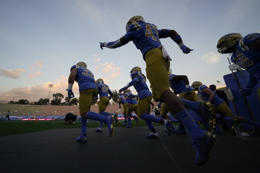 UCLA players enter the Rose Bowl before their game against rival USC.