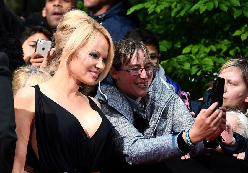 Pamela Anderson poses with a fan as she arrives to take part in a TV show last month in Paris.