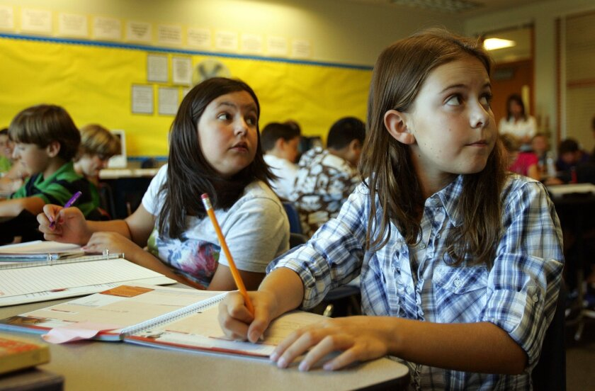 Colleen Cranny (right) and Shadi Paydar, both 11, took notes during sixth-grade English class at Marshall Middle School in Scripps Ranch. The school far exceeded its state test score goal but failed two of several federal benchmarks.