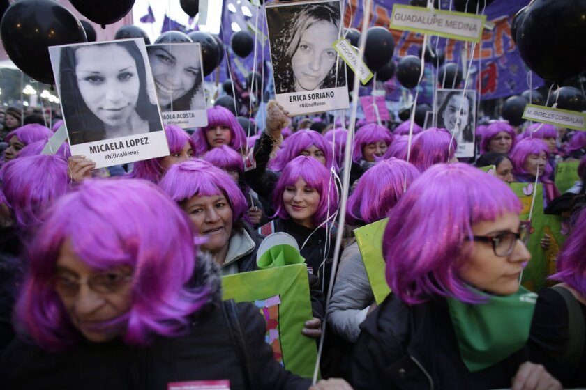 """Demonstrators holding photos of victims of gender violence march outside the National Congress in Buenos Aires, Argentina, Friday, June 3, 2016. Thousands marched under the Spanish slogan #niunamenos, which in English means """"not even one less."""" Women's rights group Casa del Encuentro reports 275 fe"""
