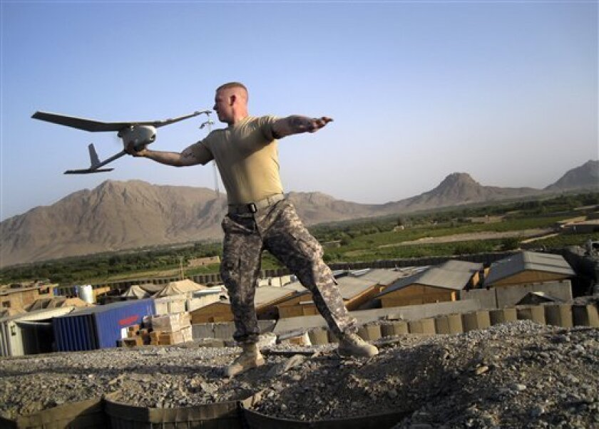 Pfc. Joseph Robinson, 20, of Eugene, Oregon, launches a 'Raven', an unmanned reconnaissance drone , at Combat Outpost Senjeray, Kandahar province, Afghanistan, Saturday, Sept. 11, 2010. (AP Photo/ Todd Pitman)