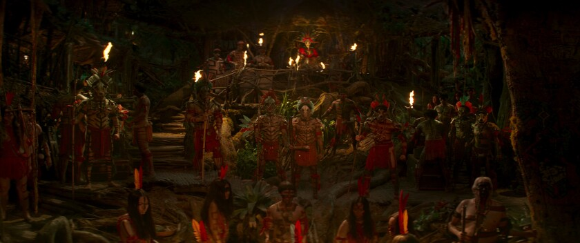 People in tribal garb dance in a line surrounded by fire torches