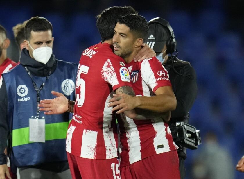 El uruguayo Luis Suárez, del Atlético de Madrid, recibe un abrazo de su compañero Stefan Savic, tras la victoria sobre el Getafe en un duelo ante el Atlético de Madrid, el martes 21 de septiembre de 2021 (AP Foto/Manu Fernandez)