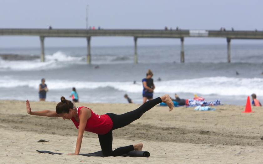 Cherelyn Steele of Pacific Beach does yoga stretches near the Ocean Beach Pier.