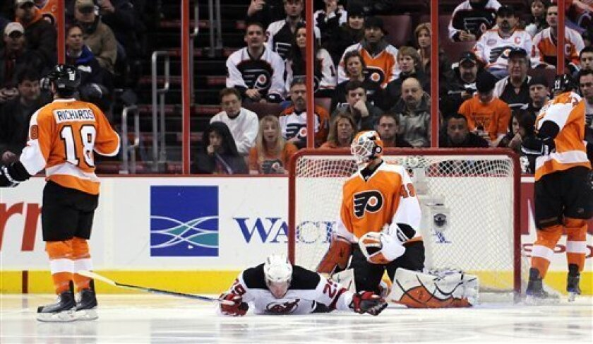 New Jersey Devils defenseman Anssi Salmela (29) of Finland lays in front of goalie Philadelphia Flyers goalie Michael Leighton (49) after scoring a goal in the second period of an NHL hockey game Monday, Feb. 8, 2010, in Philadelphia. Anssi was injured on the play. (AP Photo/Michael Perez)