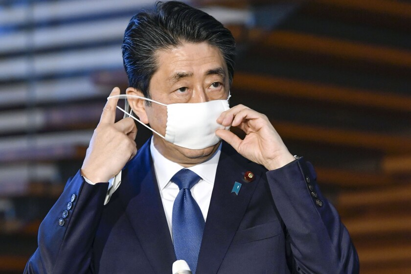 Japanese Prime Minister Shinzo Abe takes off his mask as he speaks to reporters at the prime minister's official residence in Tokyo on Monday.