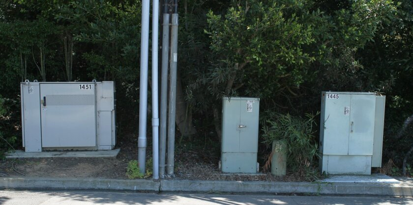 Utility boxes are sited along Rodeo Drive near La Jolla's upper Muirlands area. Overhead power lines and poles were moved underground here years ago. For safety reasons, the city says accompanying transformer and equipment boxes cannot be placed underground.