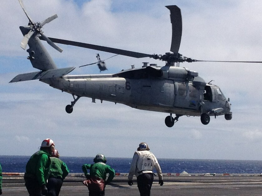 MH-60 helicopters take off from the aircraft carrier Nimitz on Wednesday, carrying Secretary of the Navy Ray Mabus and other Navy officials. The helicopters were running on a 50-50 blend of standard petroleum and biofuel made from waste cooking oil and algae.