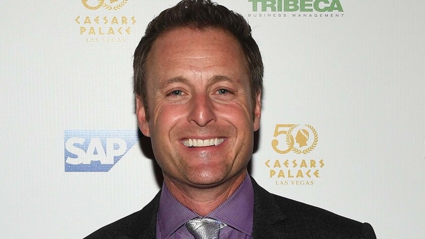 Chris Harrison smiling in a suit