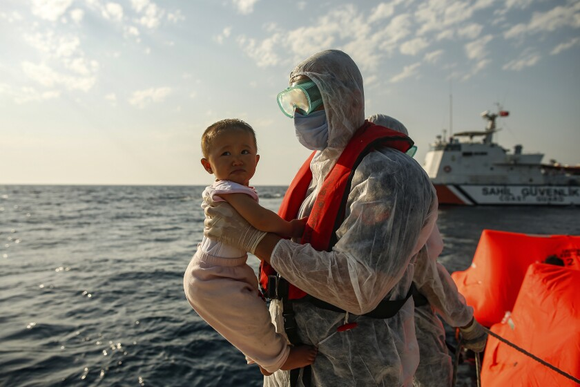"A Turkish coast guard officer, wearing protective gear to help prevent the spread of coronavirus, carries a child off a life raft during a rescue operation in the Aegean Sea, between Turkey and Greece, Saturday, Sept. 12, 2020. Turkey is accusing Greece of large-scale pushbacks at sea — summary deportations without access to asylum procedures, in violation of international law. The Turkish coast guard says it rescued over 300 migrants ""pushed back by Greek elements to Turkish waters"" this month alone. Greece denies the allegations and accuses Ankara of weaponizing migrants. (AP Photo/Emrah Gurel)"