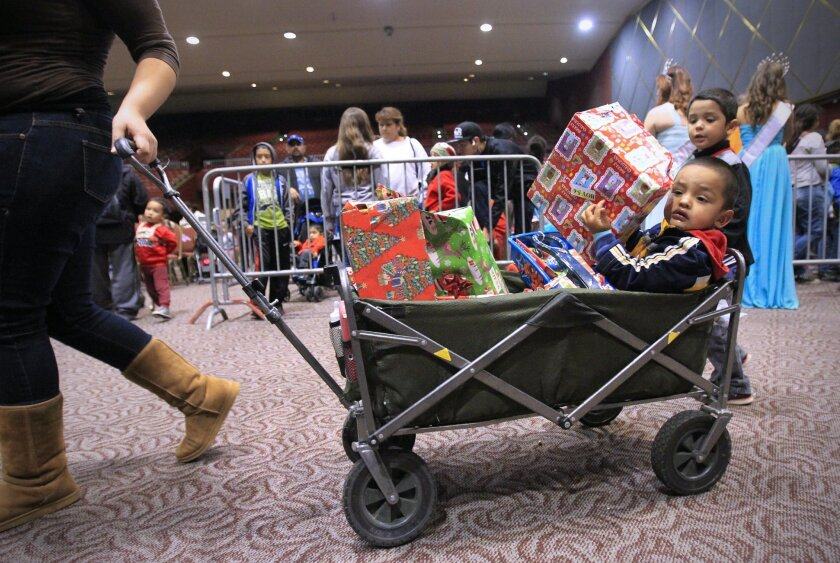 "Two-year-old Derek Diaz is surrounded by the gifts he and his brothers received during the annual ""Holiday Magic for Kids"" Christmas Party sponsored by the San Diego Coalition for the Homeless and held at Golden Hall as his mom, Sylvia Garcia pulls him in a wagon."