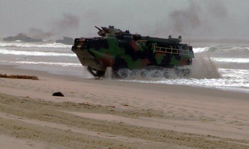 An amphibious assault vehicles plunges through the surf. Photo/AVtek Productions