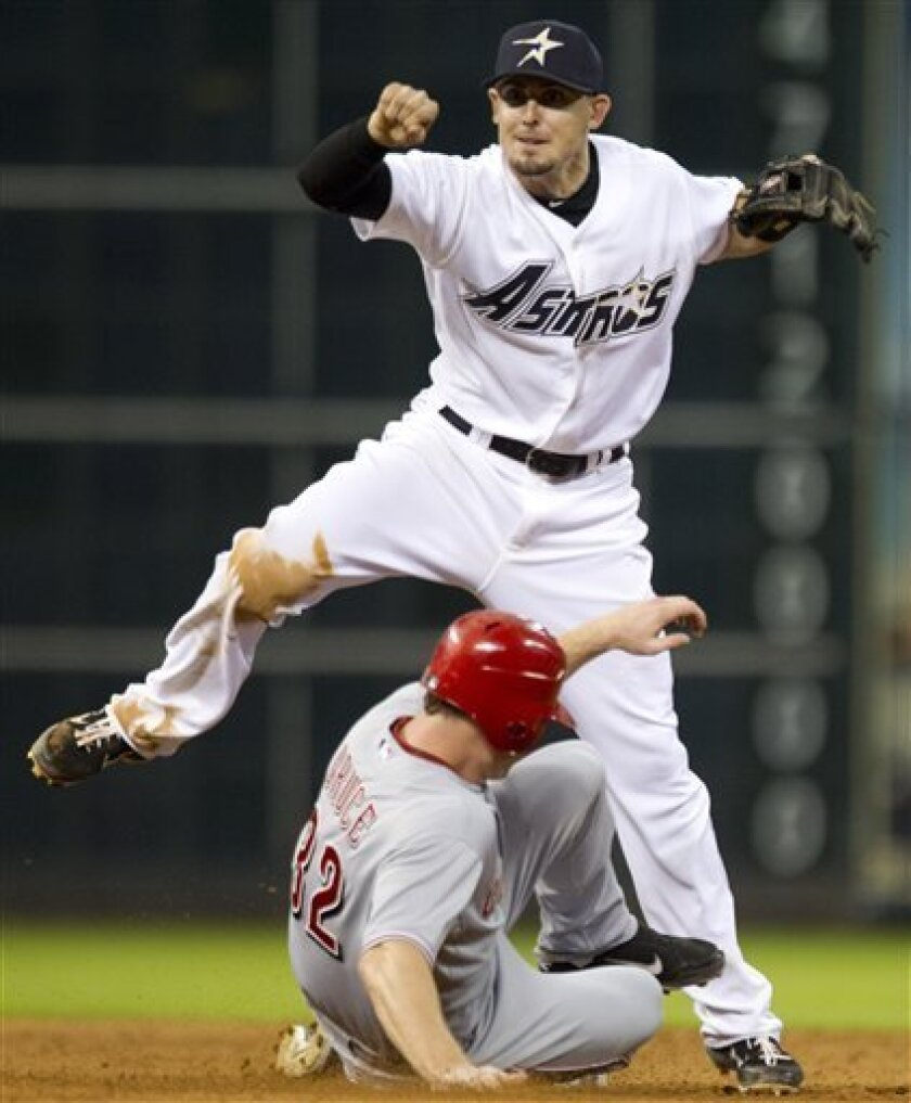 Houston Astros shortstop Tyler Greene (23) steps over Cincinnati Reds right fielder Jay Bruce (32) as he turns a double play during the seventh inning of a major league baseball game at Minute Maid Park Friday, Aug. 31, 2012, in Houston. (AP Photo/ Houston Chronicle, Brett Coomer )