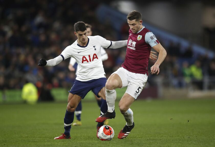 Tottenham Hotspur's Erik Lamela, left, and Burnley's James Tarkowski battle for the ball during the English Premier League soccer match at Turf Moor, Burnley, England, Saturday March 7, 2020. (Martin Rickett/PA via AP)