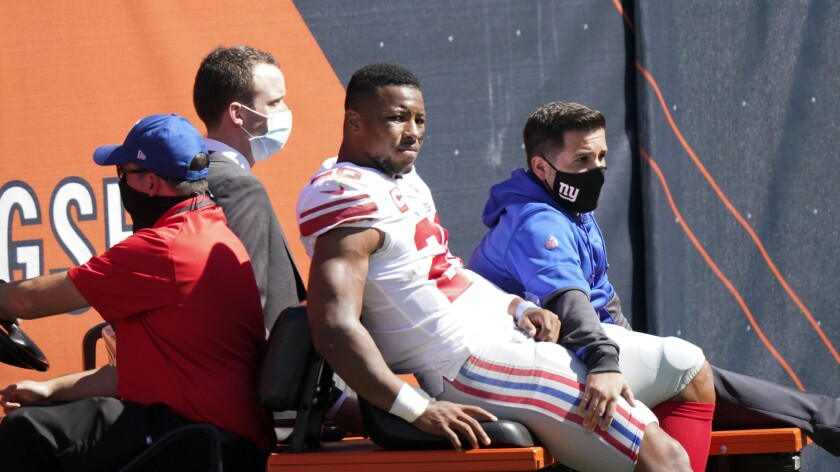 New York Giants running back Saquon Barkley (26) is carted to the locker room after being injured during the first half of an NFL football game against the Chicago Bears in Chicago, Sunday, Sept. 20, 2020. (AP Photo/Nam Y. Huh)