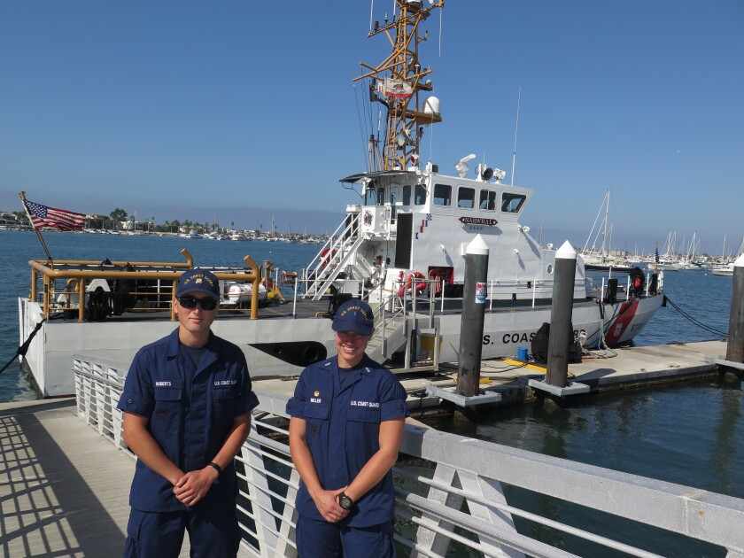 Lt. j.g. Caroline Miller, right, commanding officer of the Coast Guard cutter Narwhal, and Seaman Thomas Roberts are pictured with the 87-foot vessel at its Corona del Mar berth.