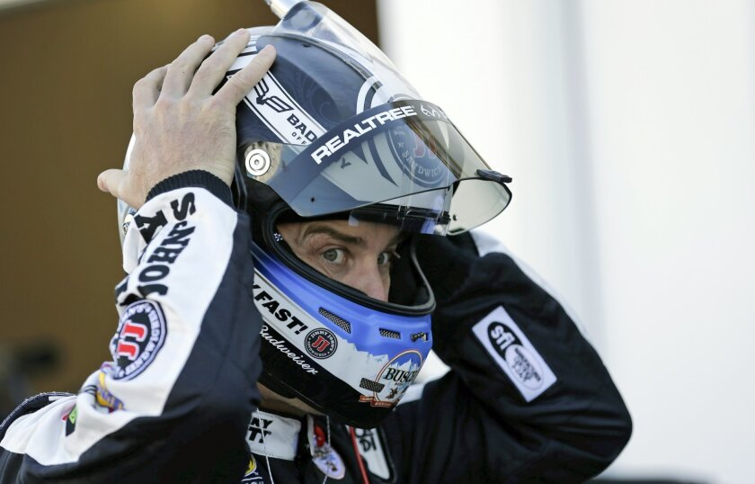 Kevin Harvick adjusts his helmet before getting in his car during a practice session for the NASCAR Daytona 500 auto race at Daytona International Speedway, Saturday, Feb. 13, 2016, in Daytona Beach, Fla. (AP Photo/Terry Renna)
