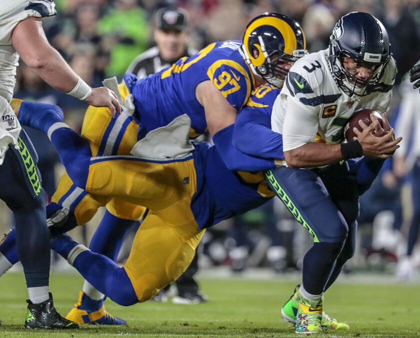 Seahawks quarterback Russell Wilson is sacked by Rams linebacker Samson Ebukam (50) and defensive end Morgan Fox in the first quarter.