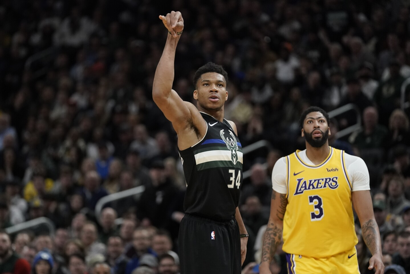 Milwaukee Bucks' Giannis Antetokounmpo makes a three-point basket in front of Los Angeles Lakers' Anthony Davis during the second half of an NBA basketball game Thursday, Dec. 19, 2019, in Milwaukee. The Bucks won 111-104. (AP Photo/Morry Gash)