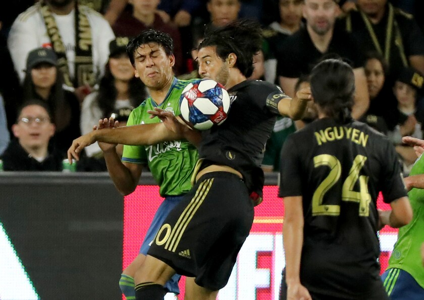 LAFC's Carlos Vela, right, battles Seattle's Xavier Arreaga for control of the ball during the first half.