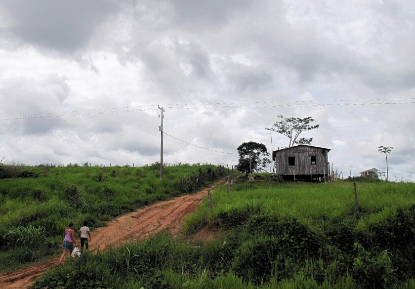 Eleven-year-old Vinicius and his mother walk to their home in the Rio Branco area of the deforested Amazon jungle after his visit with a Cuban doctor working in Brazil as part of the Mais Medicos program.