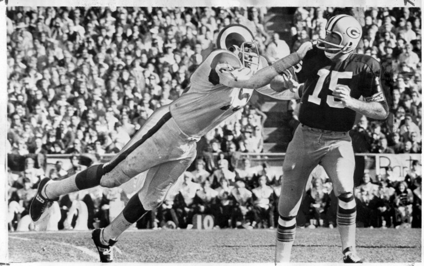 "Ram defensive end David ""Deacon"" Jones, left, forces Green Bay's Bart Starr to throw an incomplete."