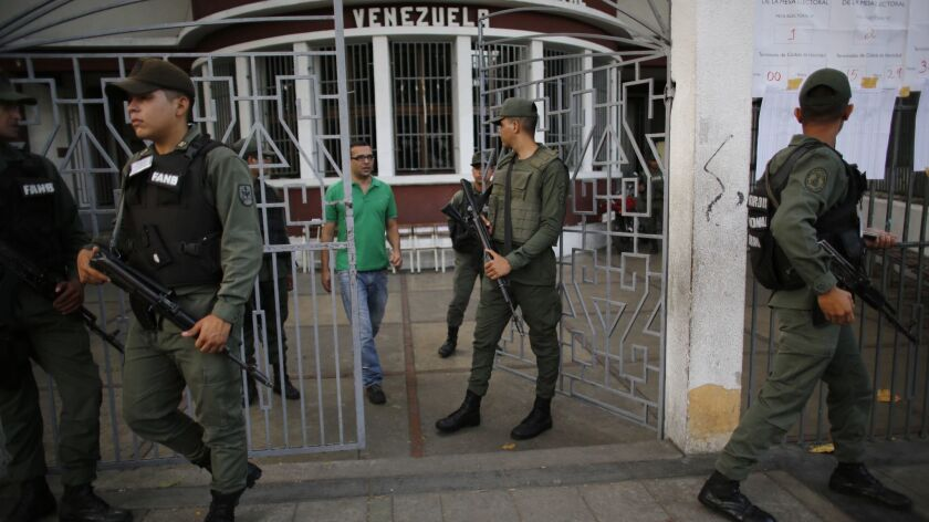 Bolivarian National Guards stand guard at a polling station during the presidential election in Cara