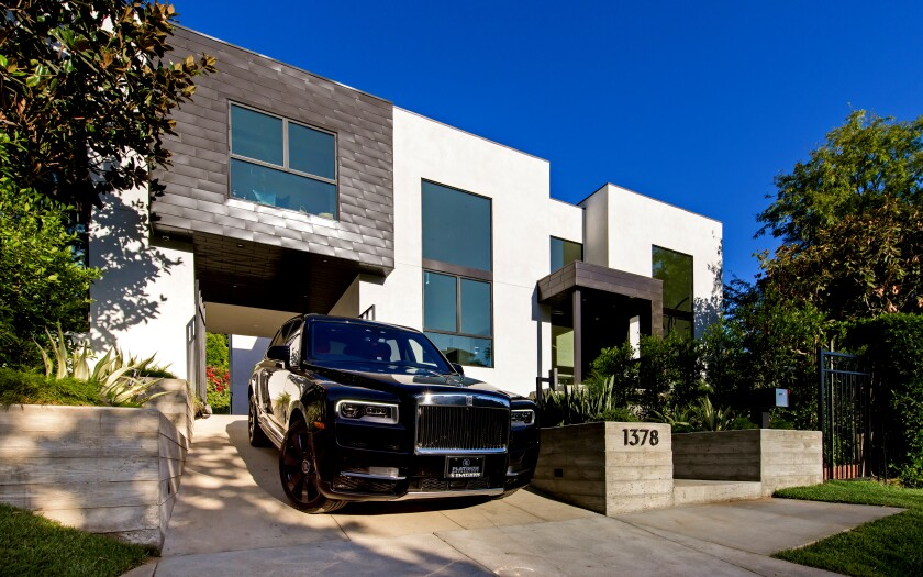 The fresh contemporary home in Hollywood Hills West is nicknamed the 'Solarium' for its voluminous step-down living room, which has a wall of steel-framed windows. Listed for $9.995 million, the multi-level house has six bedrooms and seven bathrooms in more than 6,500 square feet of space. There's also separate guest quarters. Museum-like interiors feature gallery walls and high ceilings ideal for showcasing artwork. The chef's kitchen is equipped with an island and French doors that open to the backyard. (Marc Angeles / Unlimited Style Real Estate Photography)