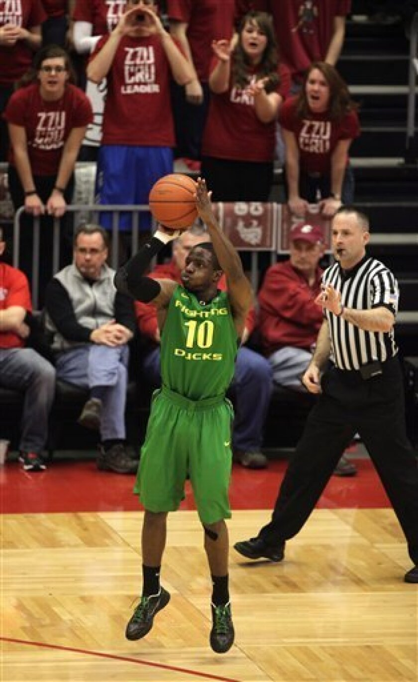 Oregon guard Johnathan Loyd (10) shoots a three-point shot from in front of the Washington State student section as referee Jeff Wooten watches during the first half of an NCAA college basketball game on Saturday, Feb. 16, 2013, at Beasely Coliseum in Pullman, Wash. (AP Photo/Dean Hare)