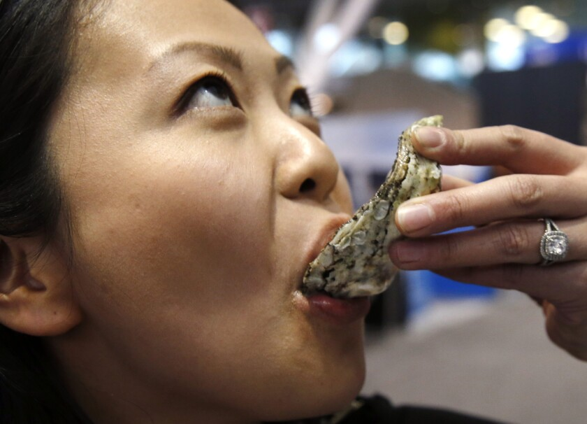 Oyster specialist Julie Qiu enjoys a sample from Blue Island Oyster Farms of New York at the 33rd Seafood Expo North America in Boston last month.