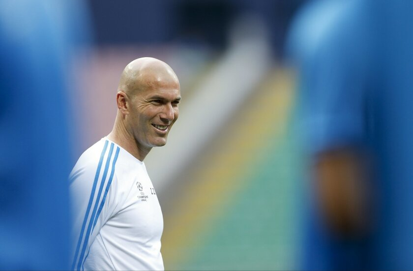 Real Madrid coach Zinedine Zidane smiles during a training session at the San Siro stadium in Milan, Italy, Friday, May 27, 2016. The Champions League final soccer match between Real Madrid and Atletico Madrid will be held at the San Siro stadium on Saturday, May 28. (AP Photo/Manu Fernandez)