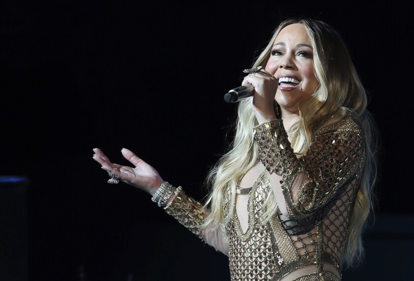 Mariah Carey sings into a microphone