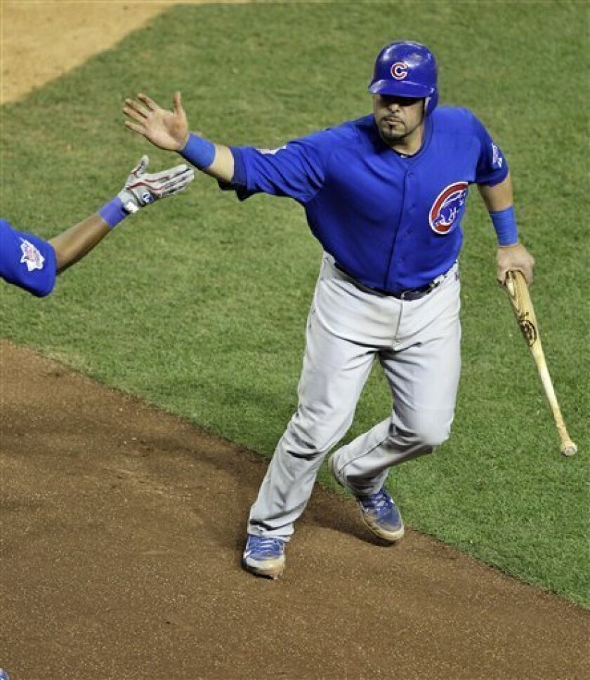 Chicago Cubs' Geovany Soto celebrates after scoring the go-ahead run on an RBI single by Darwin Barney against the Arizona Diamondbacks' during the ninth inning of a baseball game Saturday, April 30, 2011, in Phoenix. (AP Photo/Matt York)