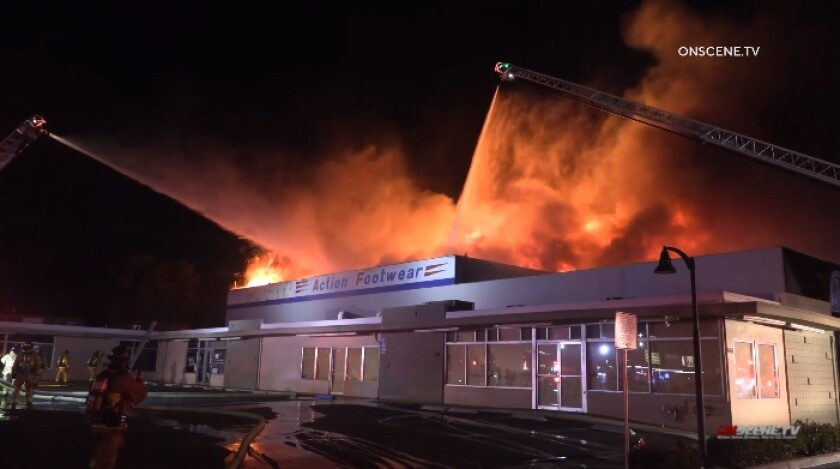Firefighters use ladders and hoses to battle a fire Monday evening at Action Footwear on H Street in Chula Vista.