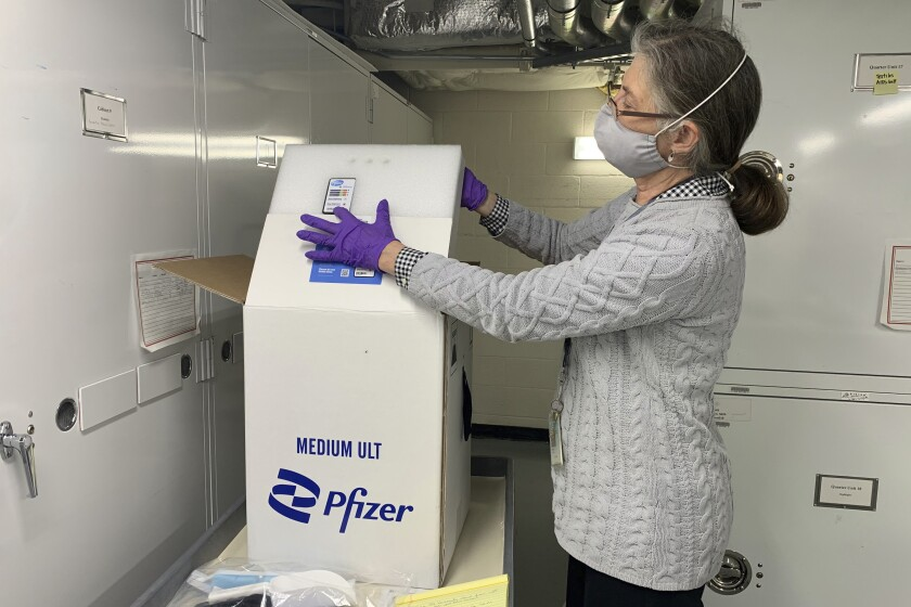 Curator Diane Wendt shows that specialized container used to ship super cold doses of the Pfizer COVID-19 vaccine in Washington, on Monday, March 8, 2021. The package and other items related to the first dose of vaccine administered in the U.S. have been donated to the Smithsonian's Museum of American History. (AP Photo/Ashraf Khalil)