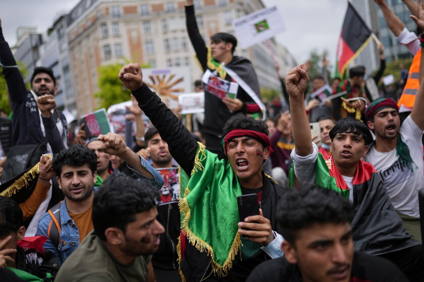 Demonstrators raise their fists during a protest to raise awareness regarding the situation in Afghanistan outside EU headquarters in Brussels, Wednesday, Aug. 18, 2021. The European Union has no immediate plans to recognize the Taliban after their sweeping victory in Afghanistan but will talk with the militants to ensure that European nationals and Afghans who have worked with the EU can leave safely, the bloc's top diplomat said Tuesday. (AP Photo/Francisco Seco)
