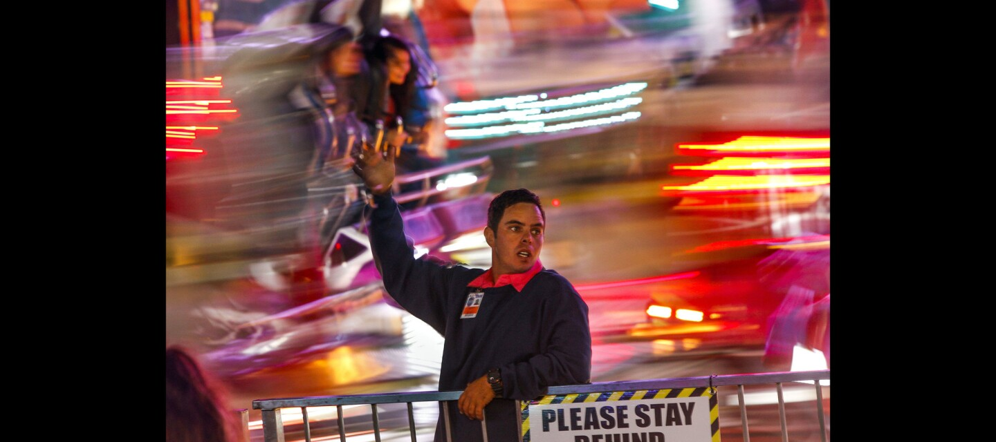 Esbach Lumile tries to lure people to the Magnum as fairgoers on the ride are whirled around behind him.
