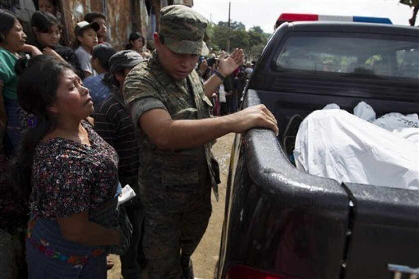 A woman watches as bodies of victims of an attack are taken away by police in San Jose Nacahuil, on the outskirts of Guatemala City, Sunday, Sept. 8, 2013. Men firing from a car poured gunshots into three cantinas in this rural town, killing at least 10 people and injuring 19, local firefighters said Sunday. (AP Photo/Moises Castillo)