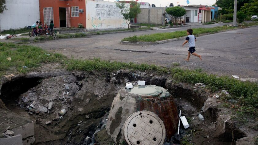 A child walks near a crater in Homex's Colinas de Santa Fe development in Veracruz, Mexico, in 2016. The SEC has filed civil charges against four former top Homex officials but has been unable to deliver a summons to them.